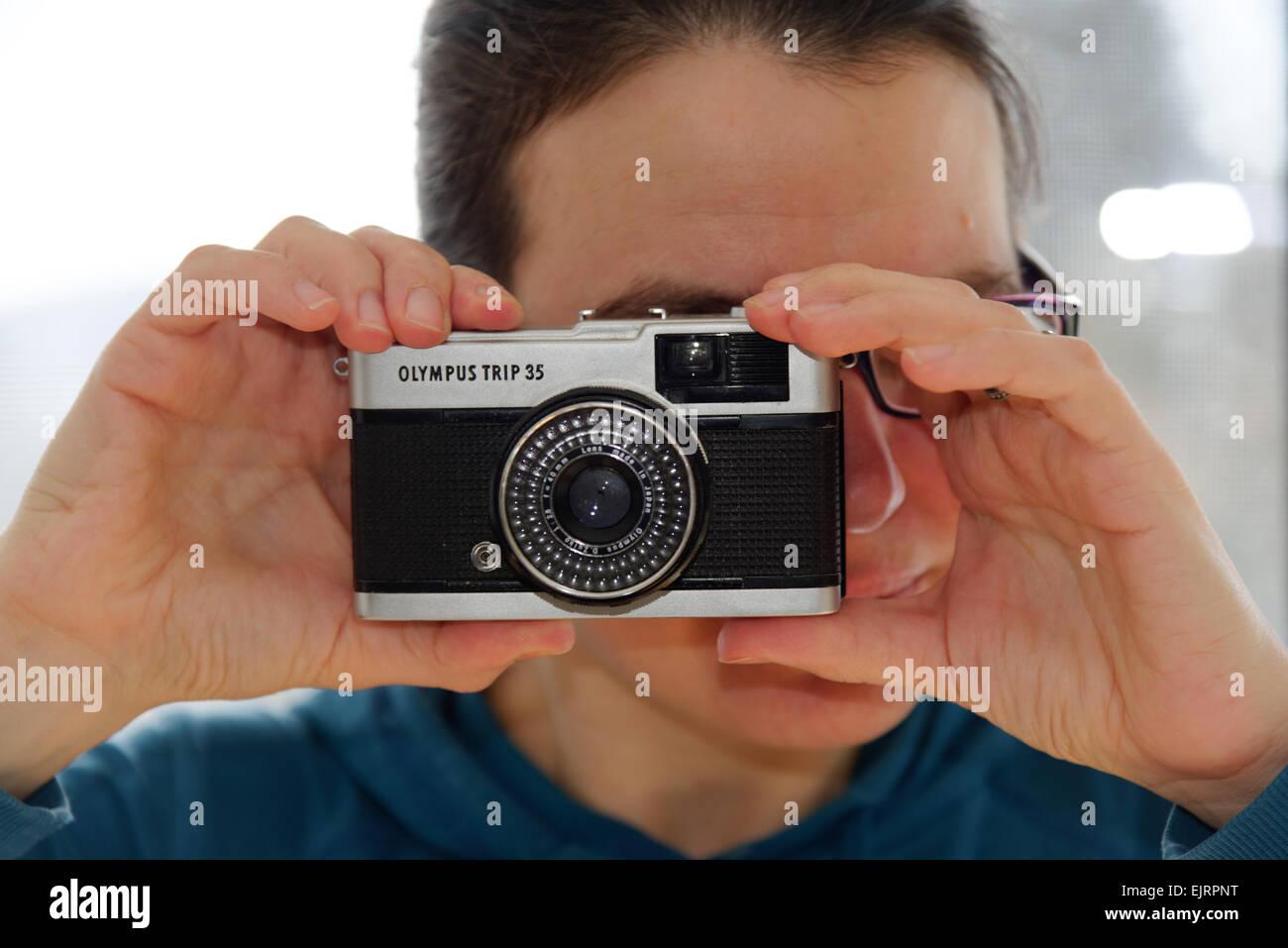 Una mujer que sostiene el clásico viaje 35 cámara compacta Olympus Imagen De Stock
