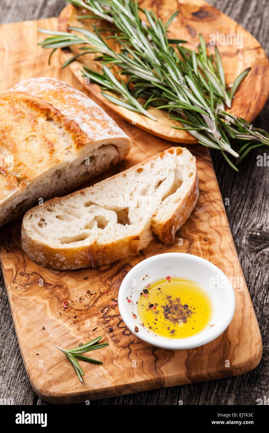 Rebanadas de pan ciabatta y aceite de oliva virgen extra Aceite de oliva utensilios de madera antecedentes Imagen De Stock