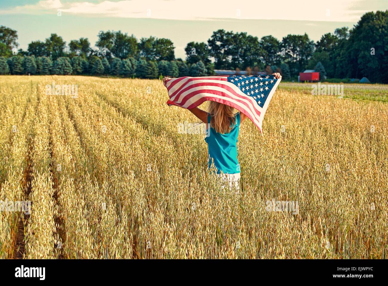 Niña corriendo en un campo de trigo con la bandera americana. Imagen De Stock