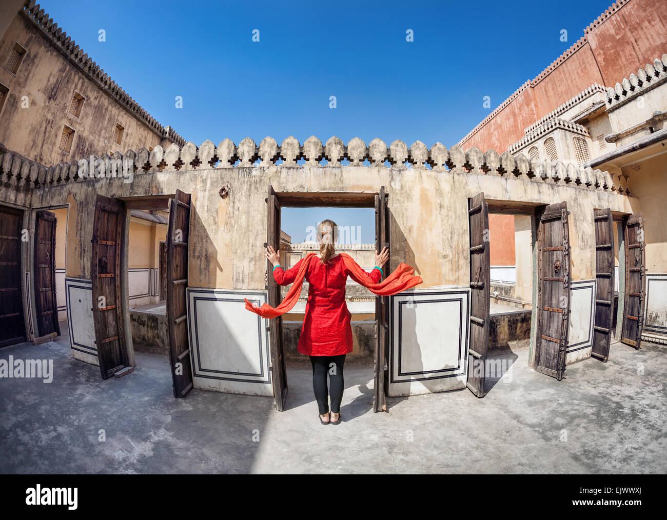 Mujer de vestido rojo con bufanda abriendo la puerta en el Hawa Mahal, Rajasthan, India Imagen De Stock