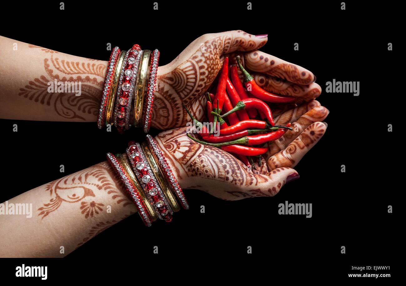 Mujer de manos con henna mantiene aisladas de chili rojo sobre fondo negro con trazado de recorte Imagen De Stock