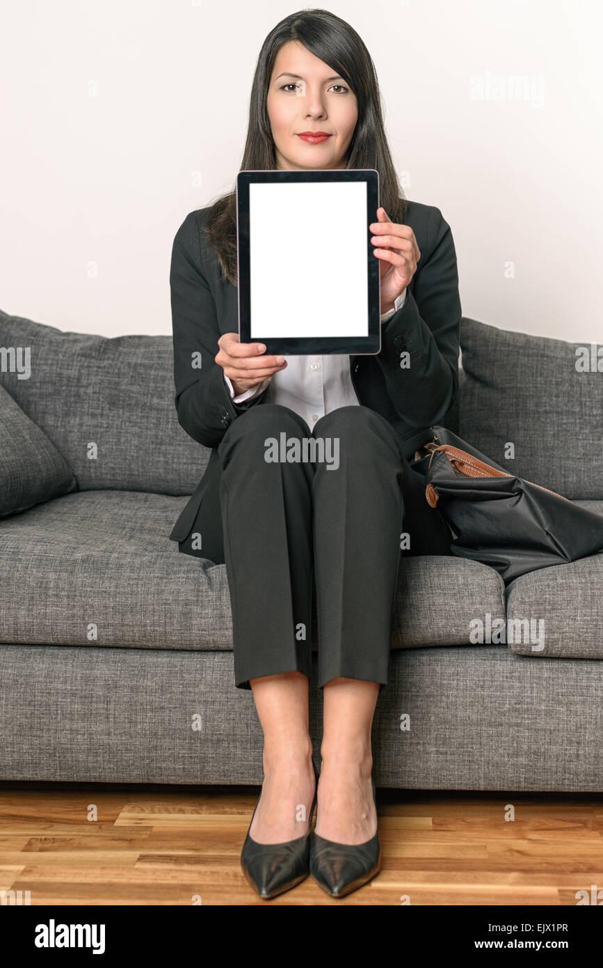 Joven Empresaria sentada en un sillón gris vacío mostrando una pantalla de Tablet PC, enfatizando el espacio de Foto de stock