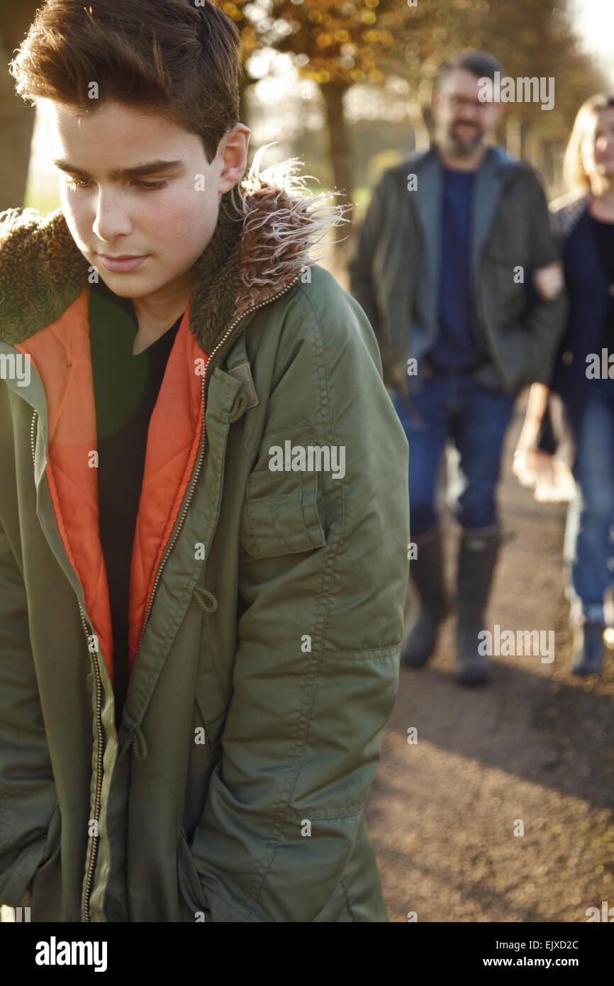 Adolescente caminando en Country Road, los padres en segundo plano. Foto de stock