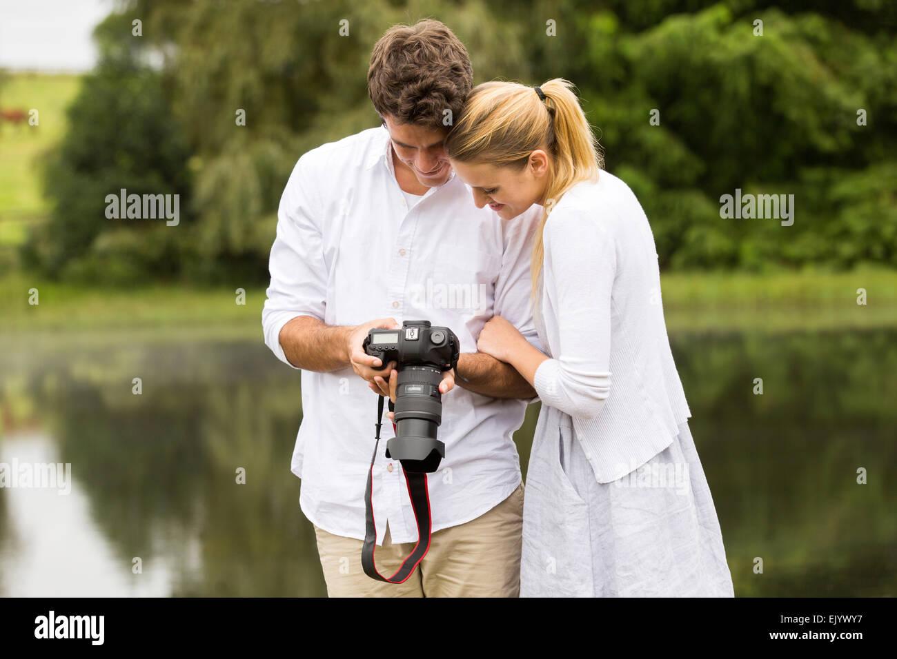 Joven pareja feliz viendo las imágenes de la cámara al aire libre Imagen De Stock