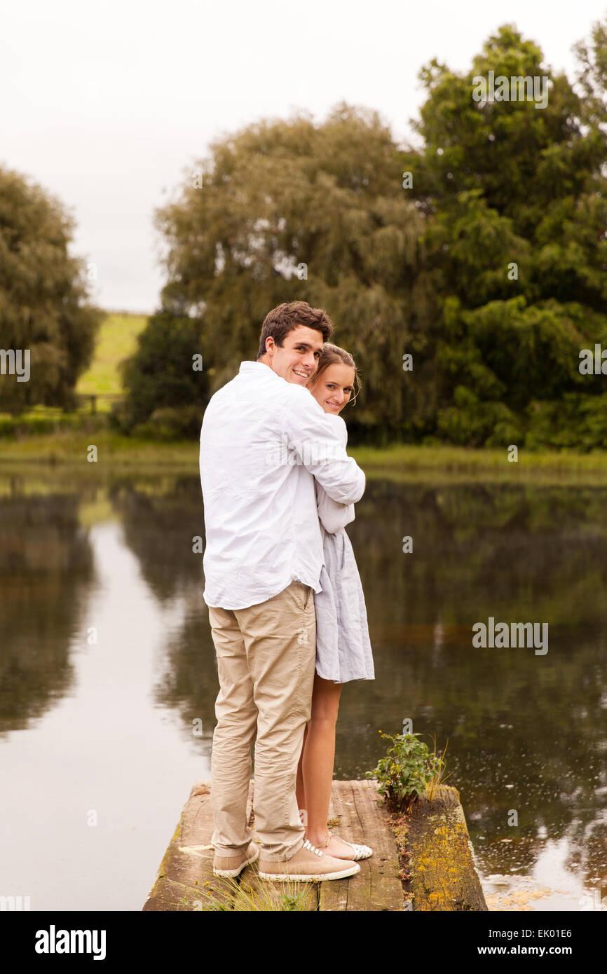 Romántica pareja joven parado en el muelle del río Foto de stock