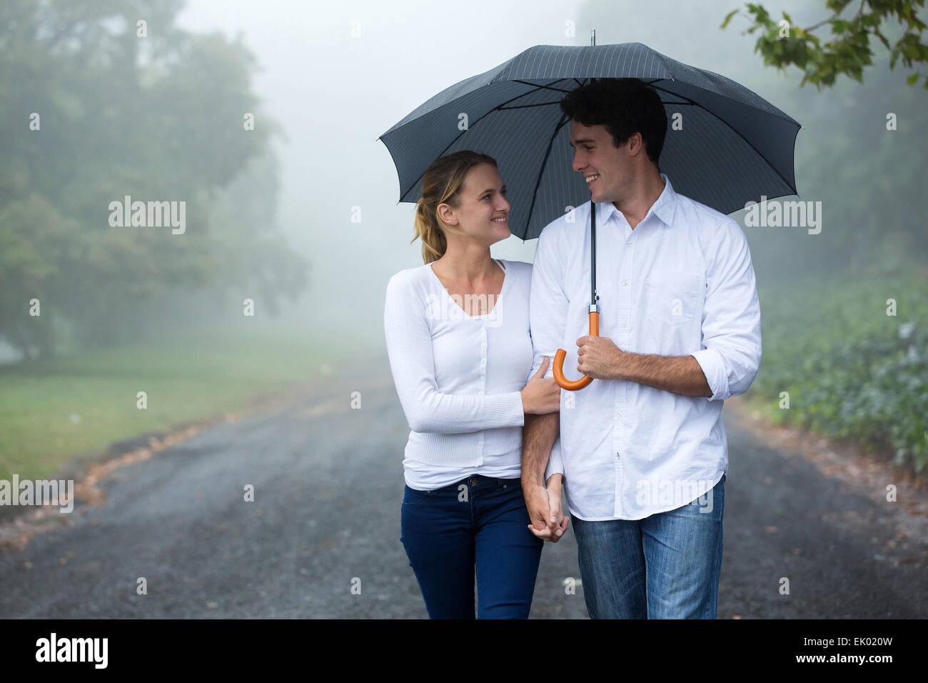 Hermosa pareja caminando bajo el paraguas en el bosque Foto de stock