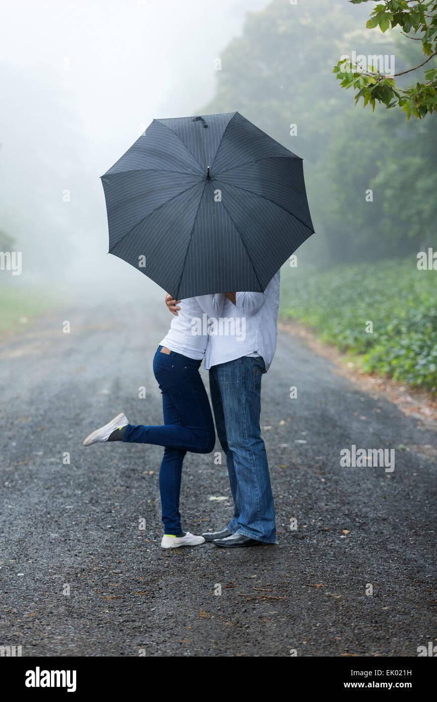 Romántica pareja joven escondiéndose detrás de los paraguas en la lluvia Imagen De Stock