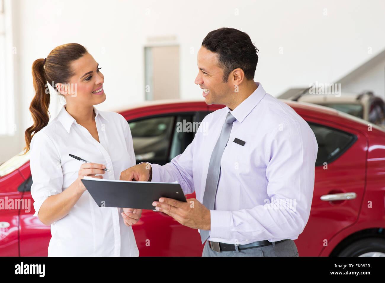 Amable vendedor de coches de mediana edad que acaba de hacer una venta a clientes jóvenes Imagen De Stock