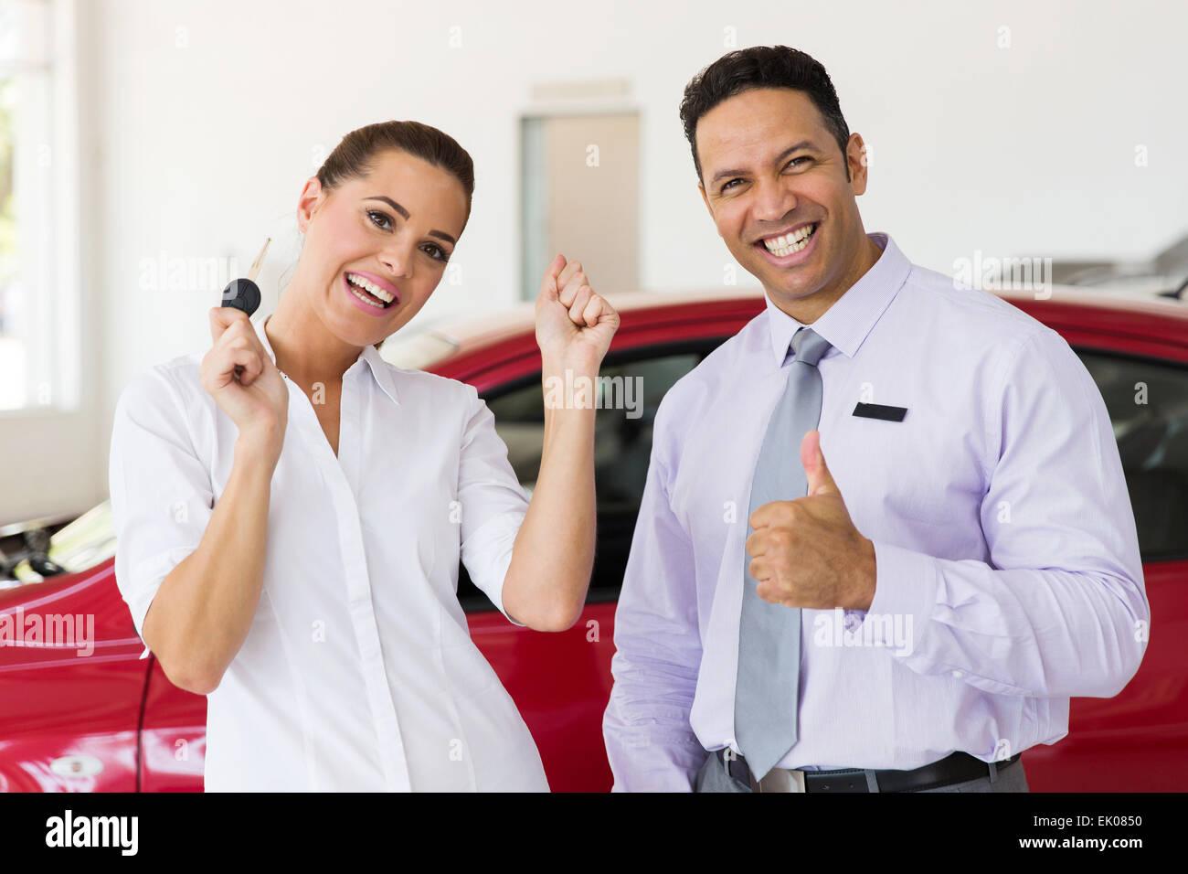 Emocionados mujer acaba de comprar un nuevo coche de concesionario Imagen De Stock