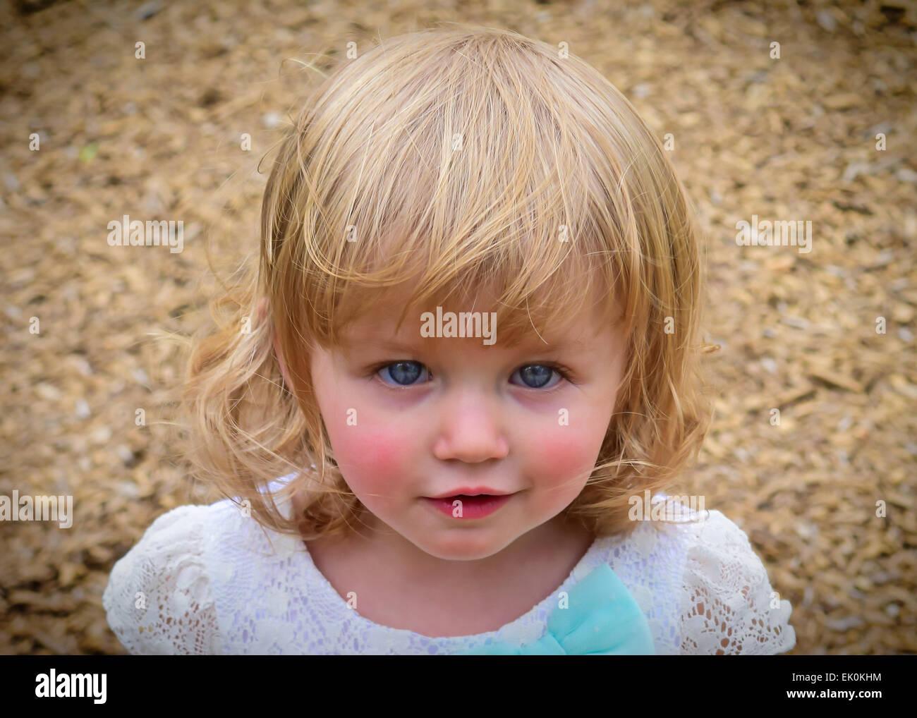 Retrato de una niña pequeña, rubia, en un parque Foto de stock