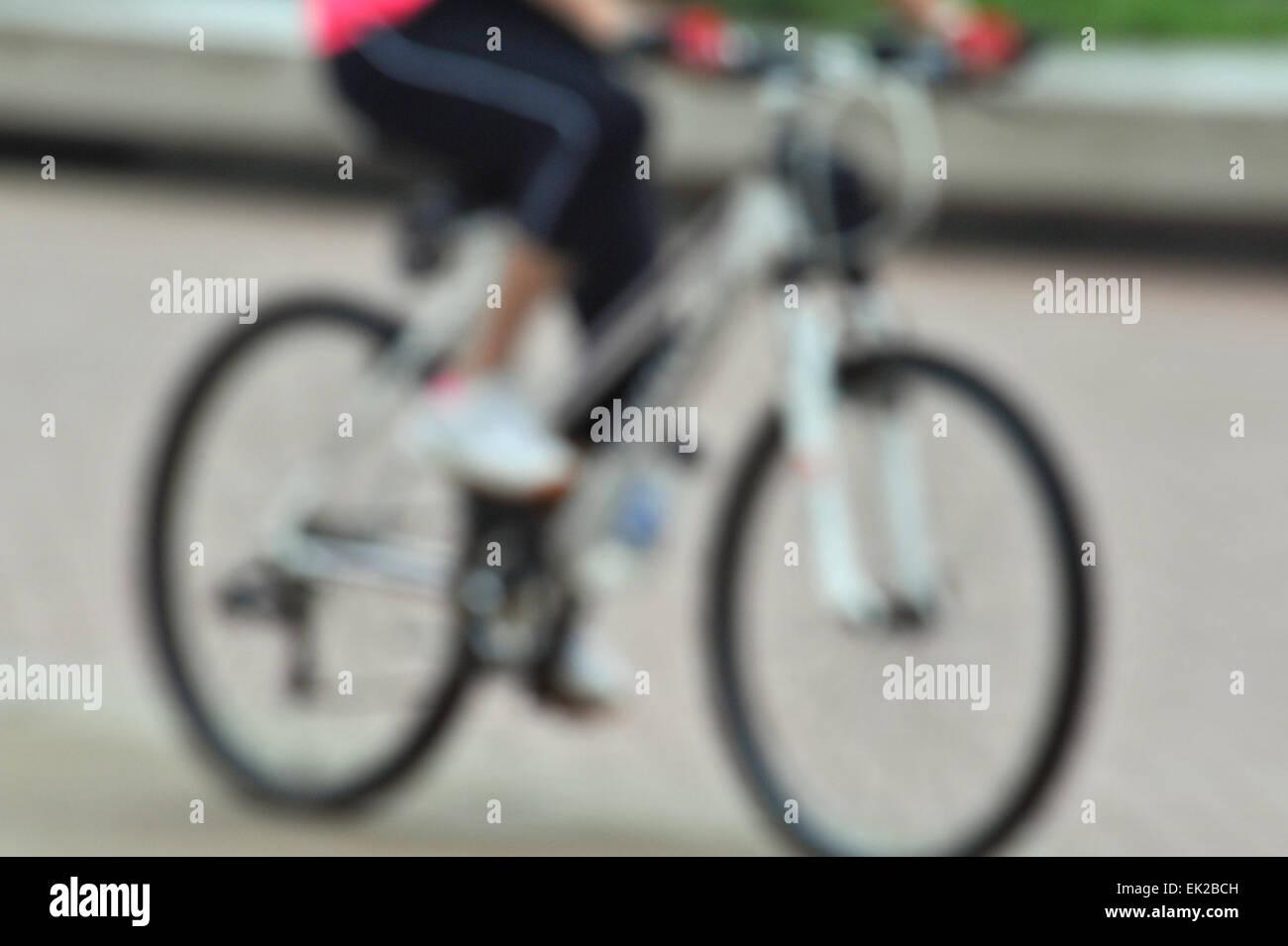 Focus blur, moviendo las piernas de una mujer adulta en bicicleta al aire libre, como parte de su rutina diaria Imagen De Stock