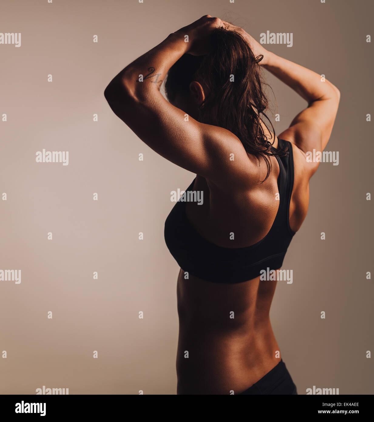 Vista trasera del joven culturista mostrando cuerpo musculoso. Hembra de Fitness muscular mostrando hacia atrás. Imagen De Stock
