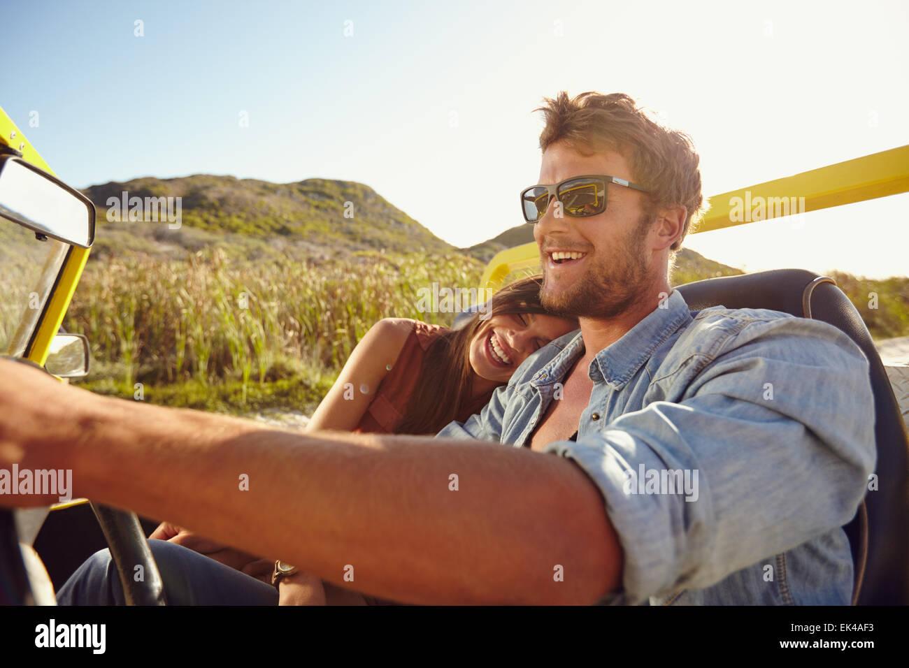 Joven pareja feliz yendo de vacaciones juntos en un buggy car. Tierna pareja disfrutando en un viaje por carretera. Imagen De Stock