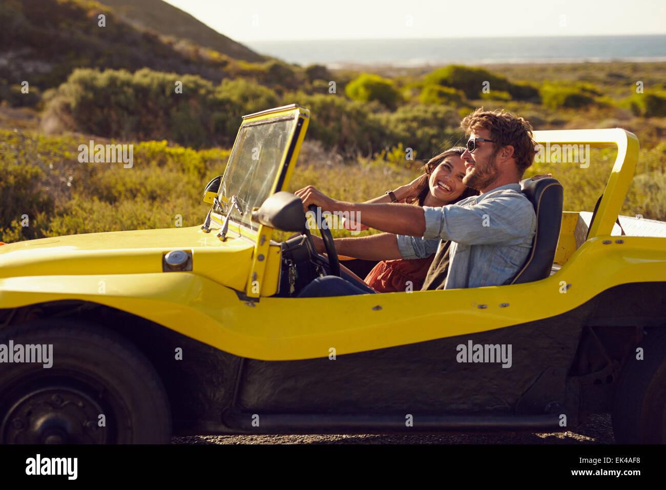 Sonriendo par ir de vacaciones juntos en un día de verano. Joven con su novia en un viaje por carretera en Imagen De Stock