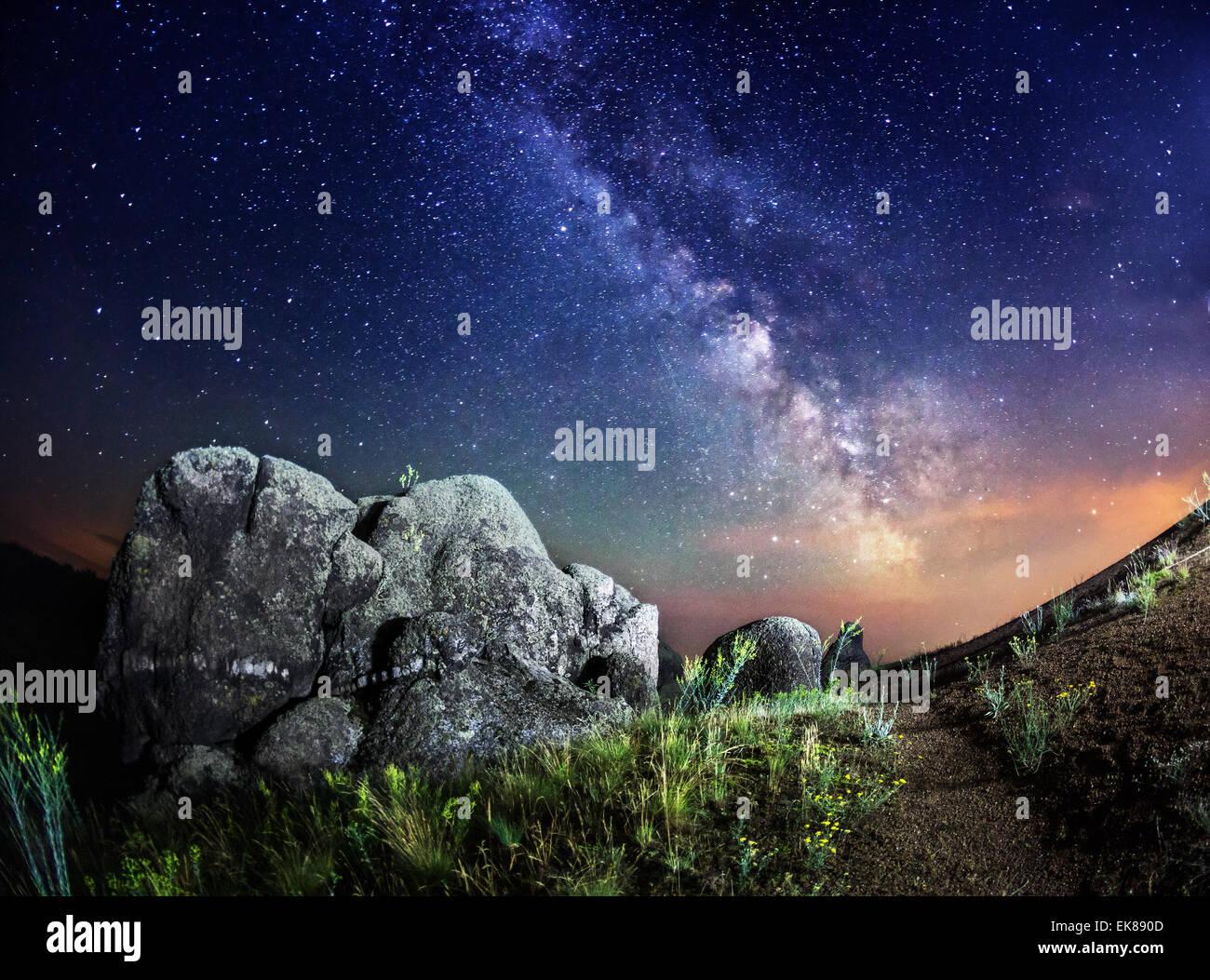 Vía Láctea. Noche de verano hermoso cielo con estrellas, rocas, trail y plantas verdes en Ucrania Imagen De Stock