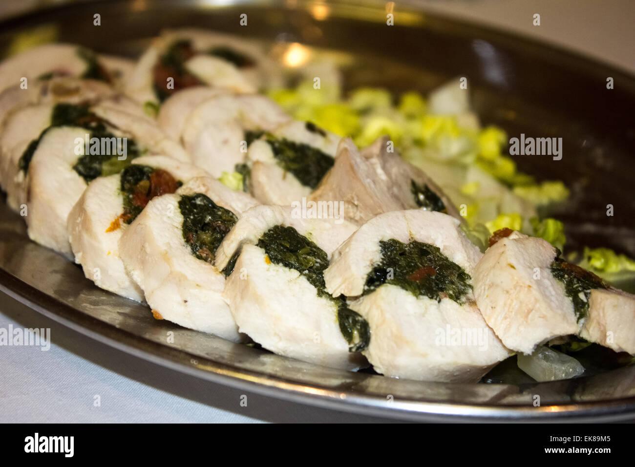 Canapés de pollo rellena con espinacas y salsa de arándano con lechuga en el lateral sobre una placa en Imagen De Stock