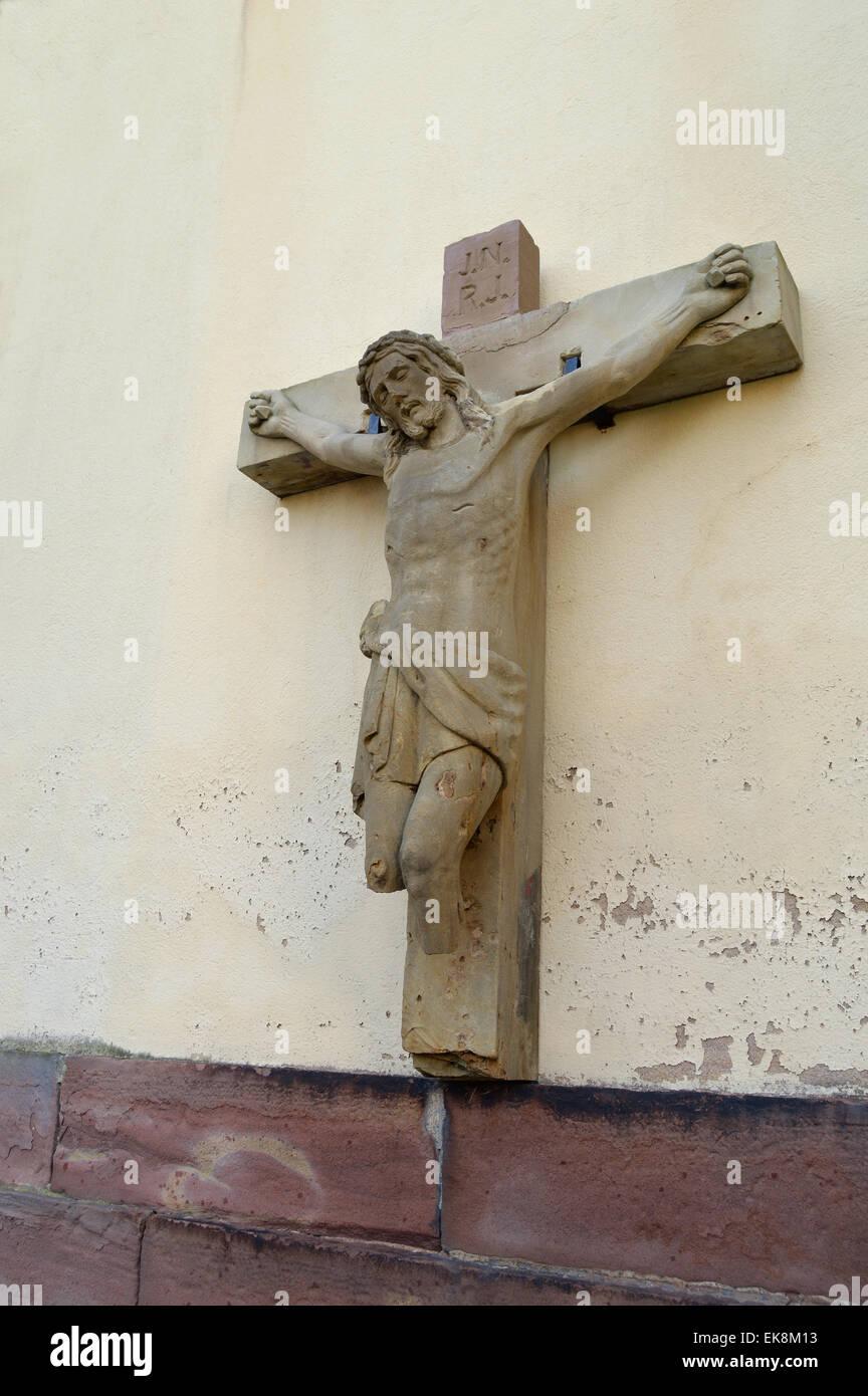 Dañado estatua de Jesús en la cruz sin piernas en una pared de la iglesia en la región de Alsacia, Francia Foto de stock