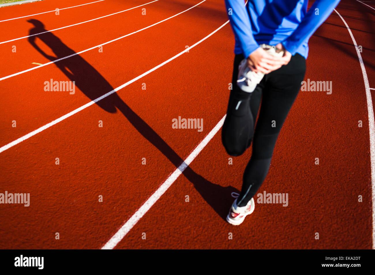 Mujer joven estiramientos antes de correr vaciados Imagen De Stock