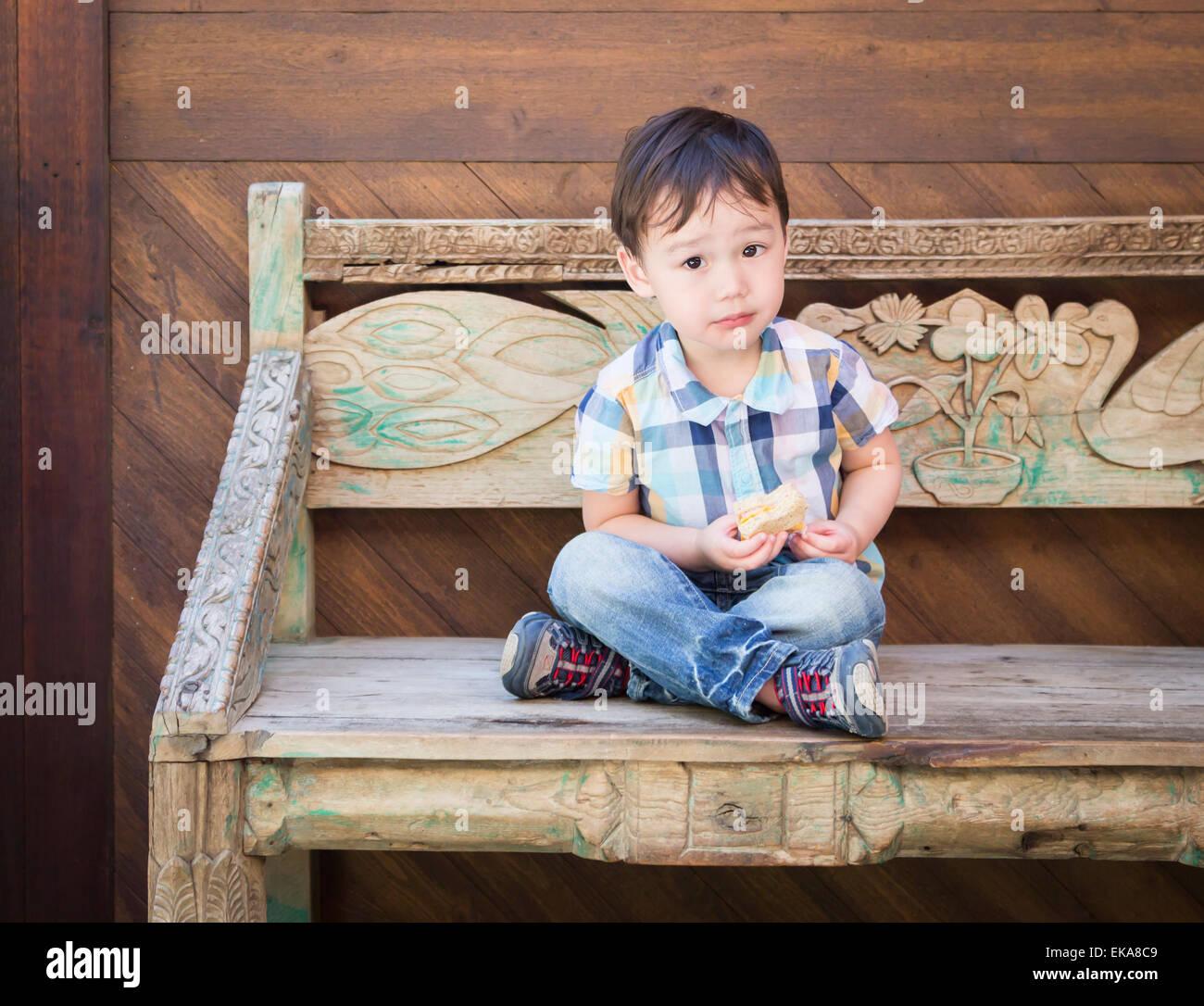 Cute relajado Mestizos muchacho sentado en un banco comiendo su sándwich. Imagen De Stock