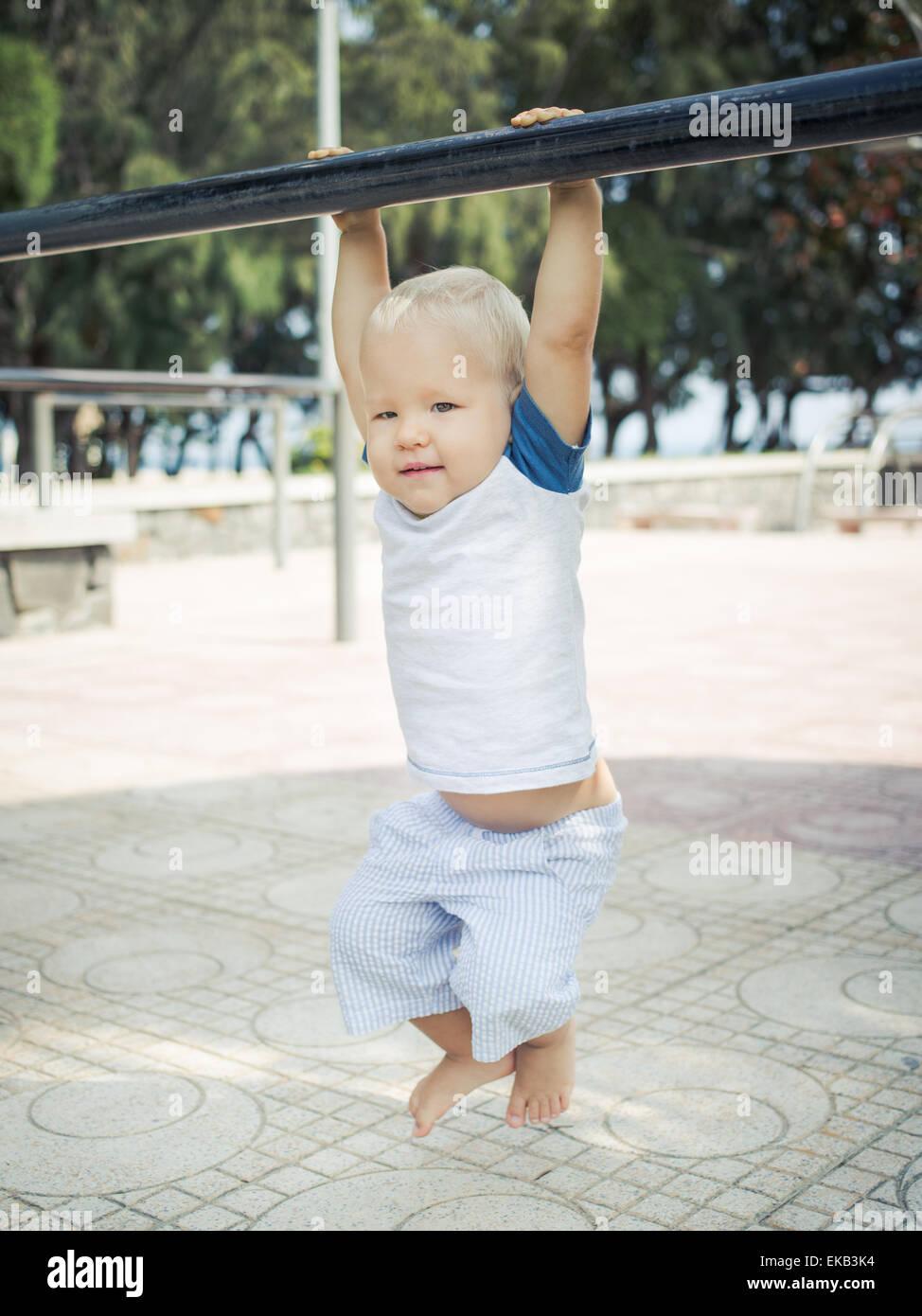 Bebé colgando de un pull-up bar Imagen De Stock