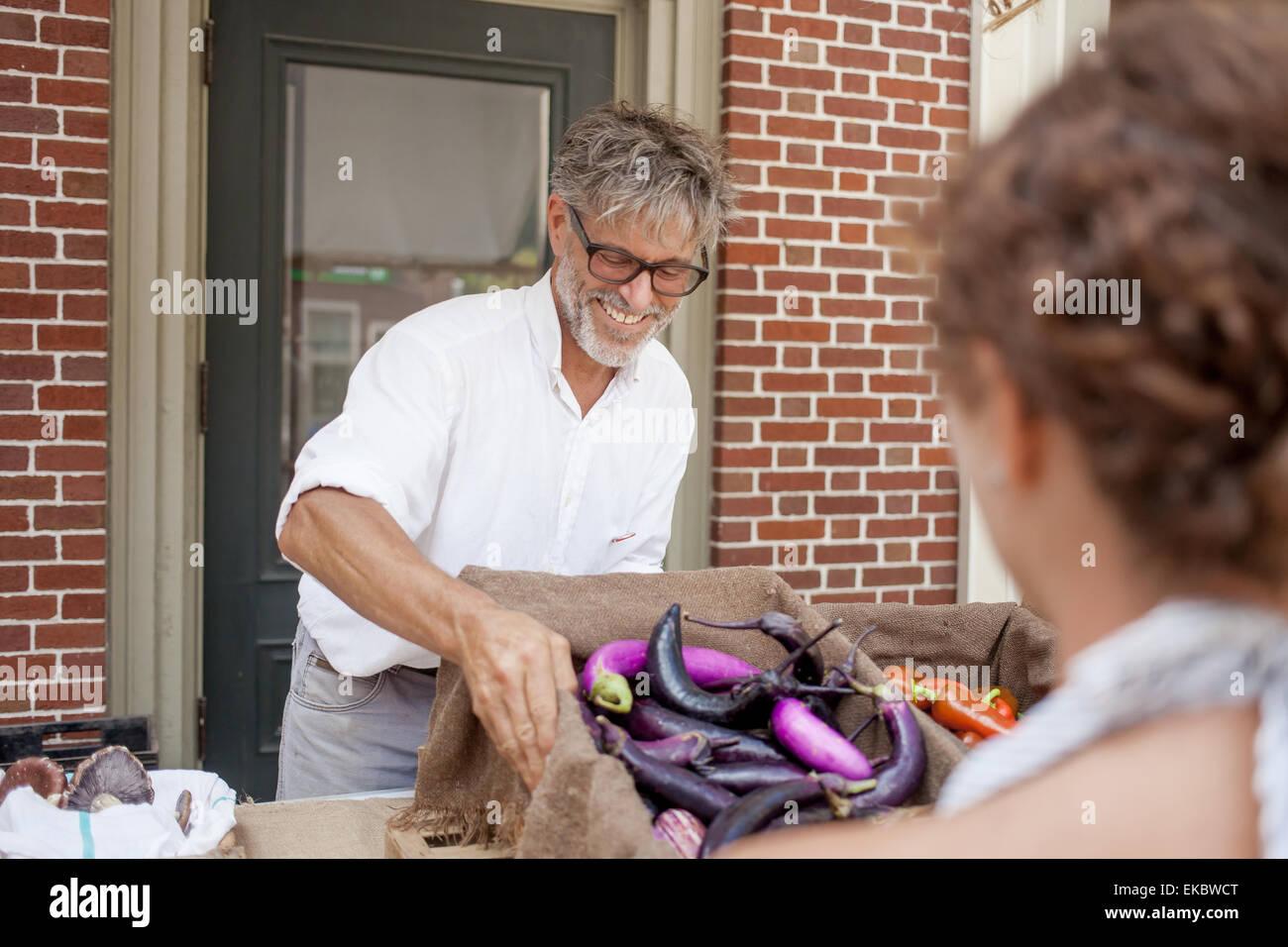 Agricultor vendiendo orgánica berenjenas en cala Imagen De Stock