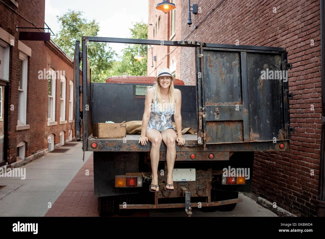 Mujer sentada sobre un camión de alimentos orgánicos del agricultor fuera de tienda de ultramarinos Imagen De Stock