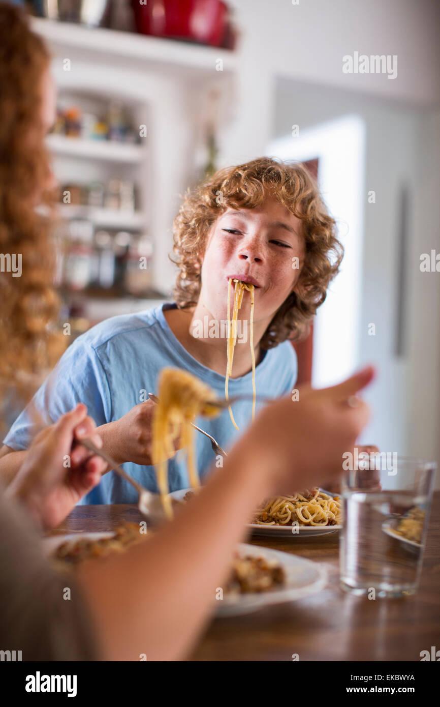 Adolescente comiendo espaguetis en mesa de comedor Imagen De Stock