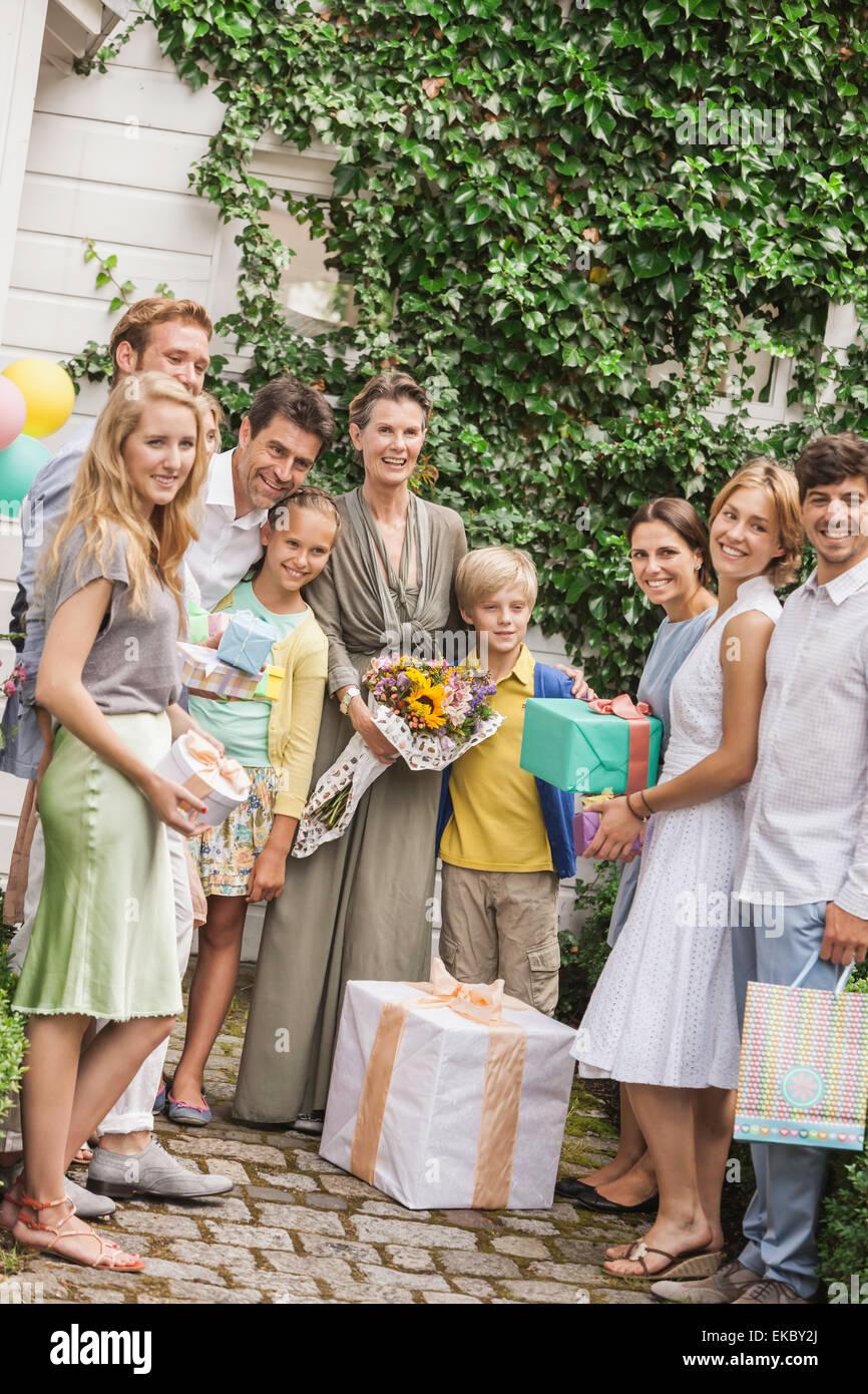 Retrato de tres generaciones de la familia jardín con bouquet y regalos de cumpleaños Imagen De Stock