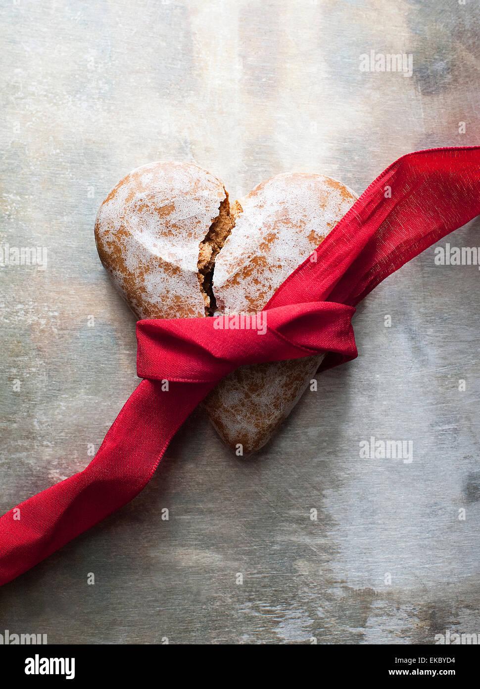 Corazón roto con forma de galleta de jengibre con una cinta roja Imagen De Stock