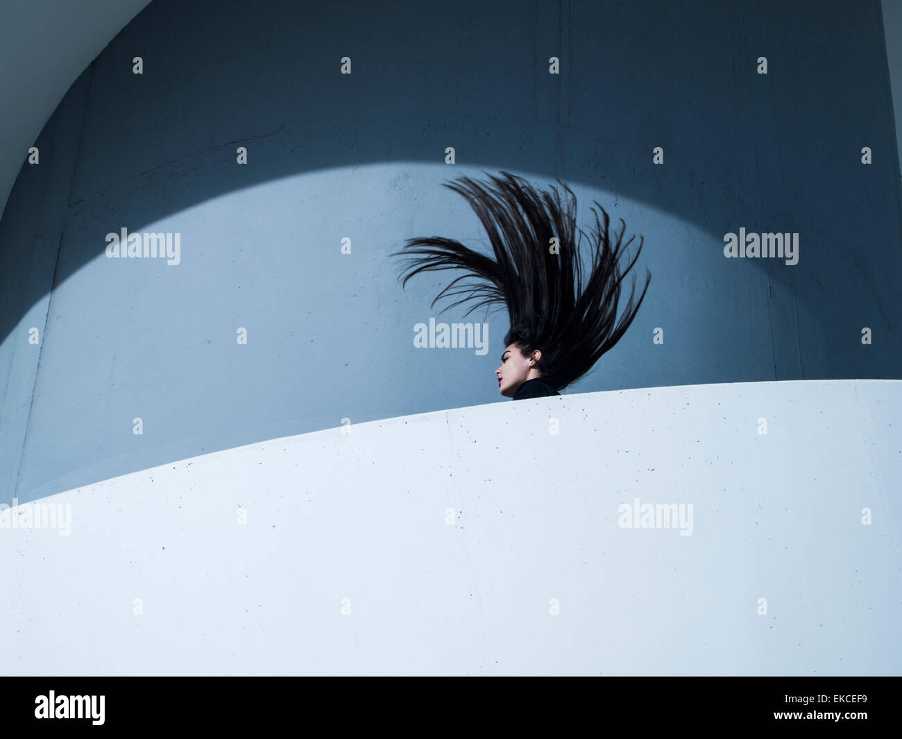 Mujer joven lanzando su cabeza hacia atrás Foto de stock