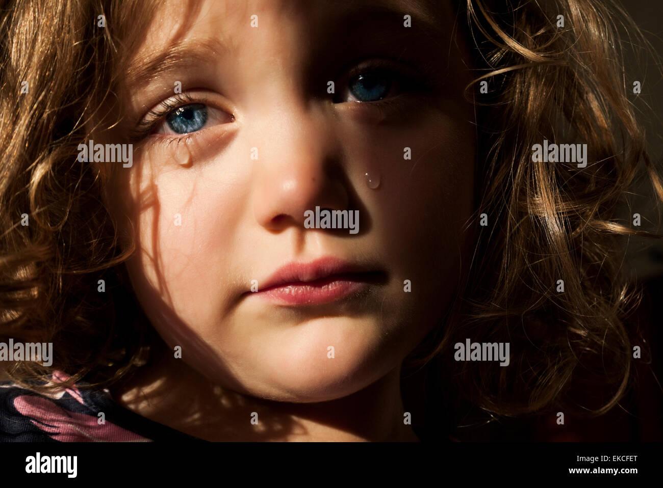 Retrato de una chica triste con ojos azules penetrantes llorando Foto de stock