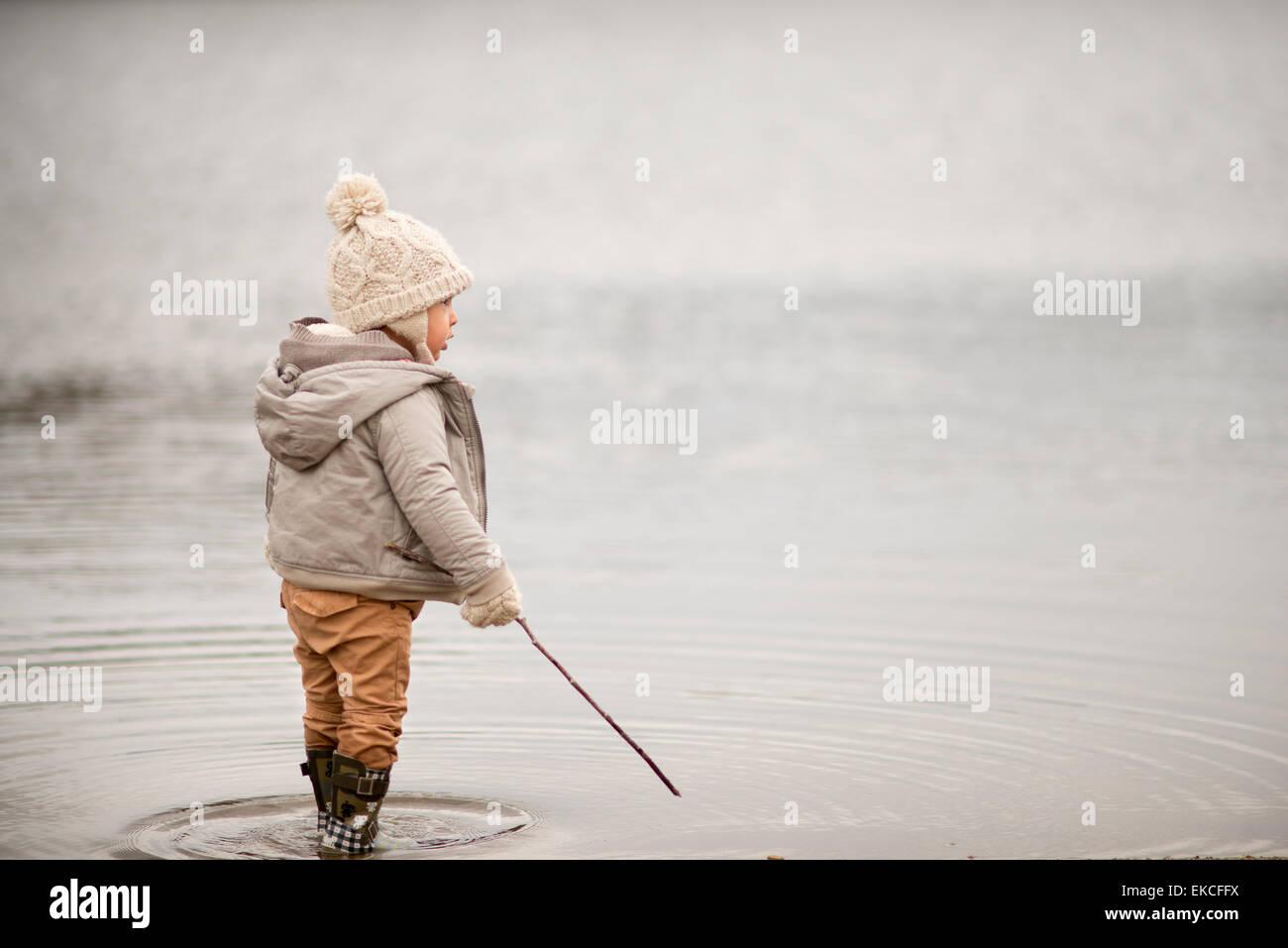 Joven de pie en un lago, sosteniendo un palo Foto de stock
