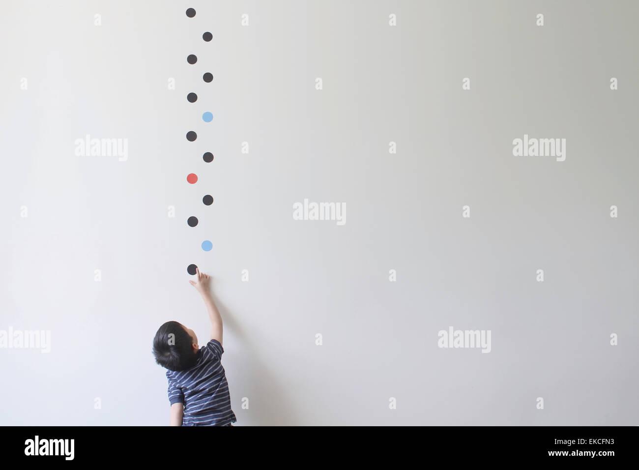 Chico tratando de elegir uno de los patrones de puntos de la pared Imagen De Stock