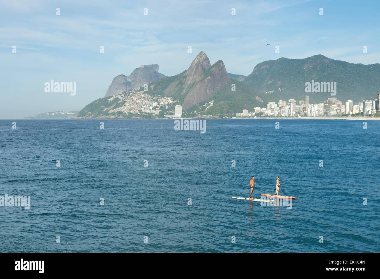 Río de Janeiro, Brasil - Marzo 22, 2015: un par de Stand Up Paddle entusiastas hacen su camino a la orilla Imagen De Stock