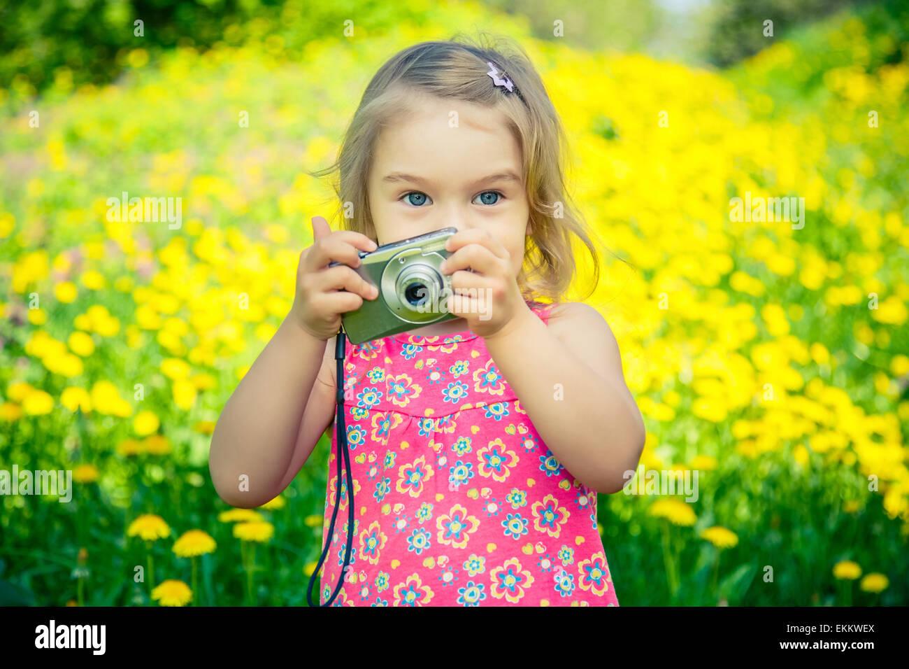 Niña tomando fotografías en una pradera Imagen De Stock