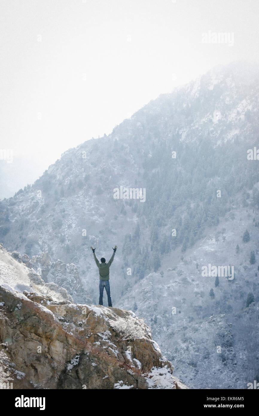 Un hombre saludo al sol, con los brazos levantados en un afloramiento rocoso en las montañas. Imagen De Stock