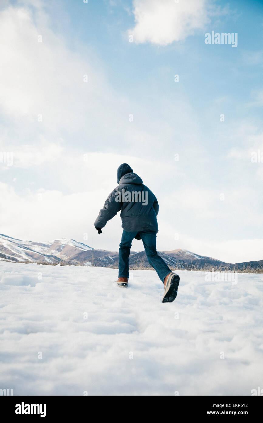 Un niño corriendo lejos a través de la nieve. Imagen De Stock