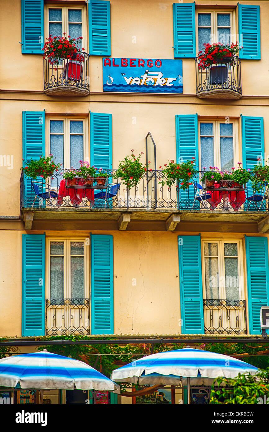 Ventanas, balcones en un pequeño hotel, Albergo Vapore, Menaggio, el Lago de Como, en Lombardía, Italia Imagen De Stock