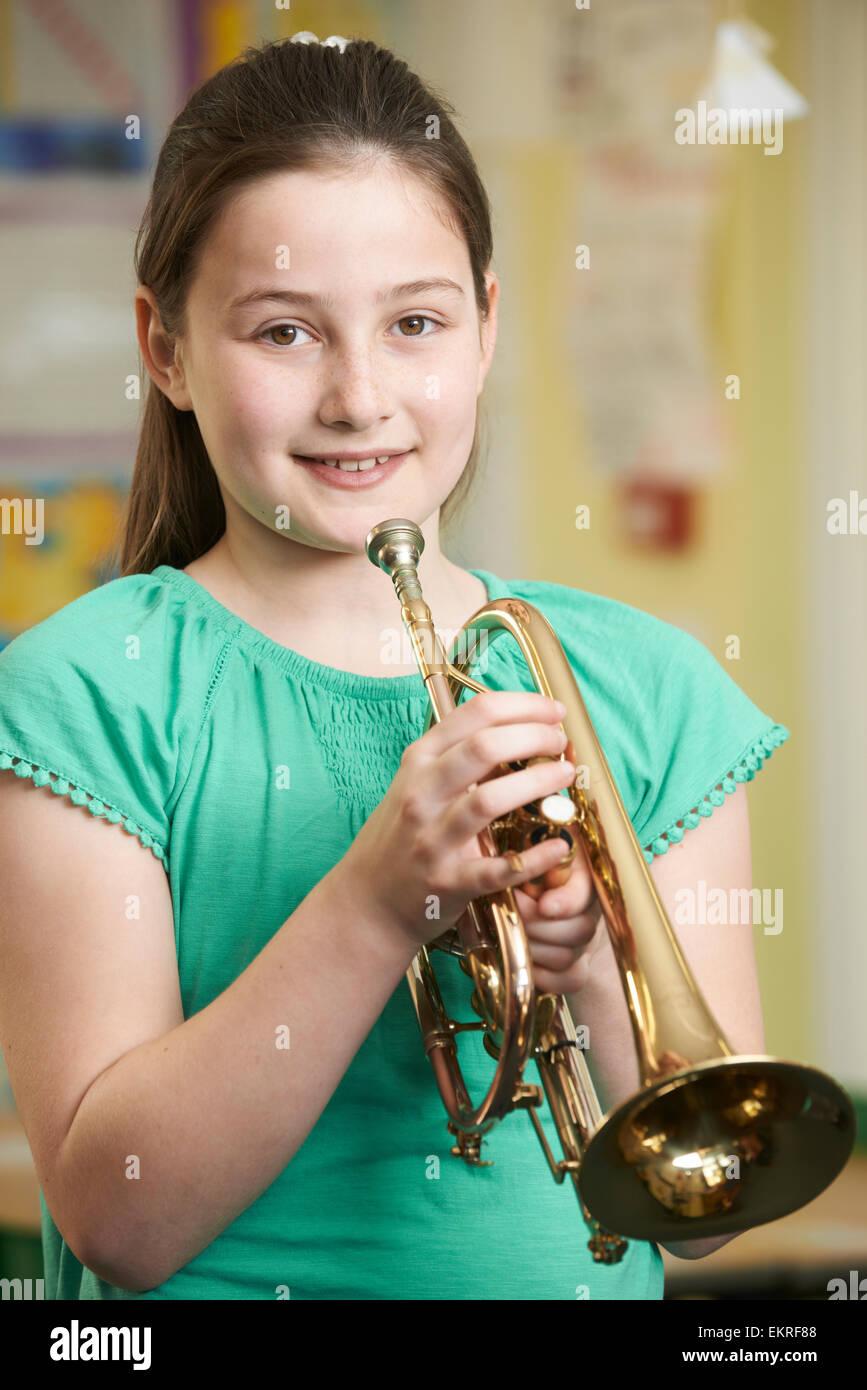 Niña aprendiendo a tocar la trompeta en la escuela Lección de música Imagen De Stock