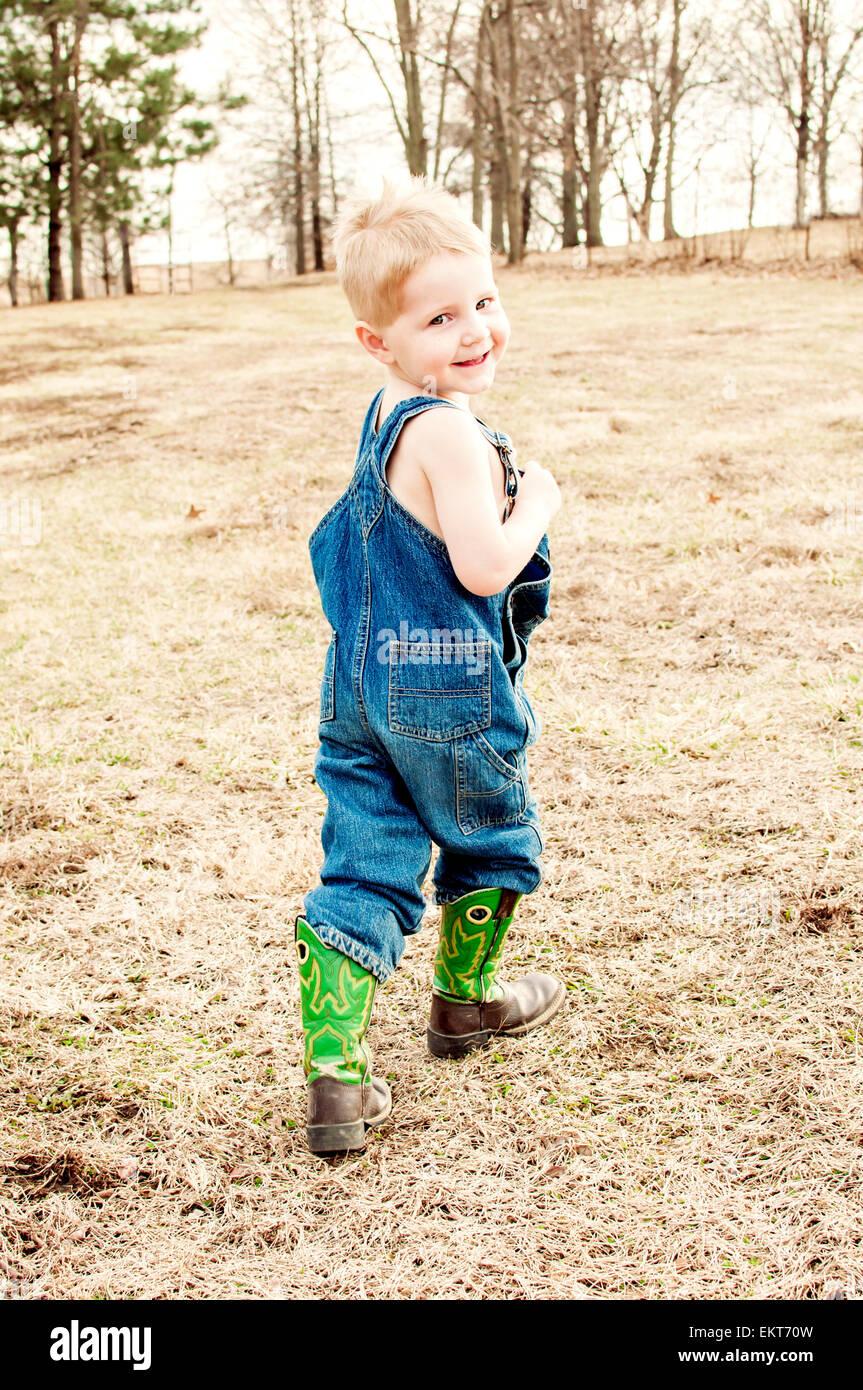 Boy en jeans overoles y botas, paseos en el país Foto de stock