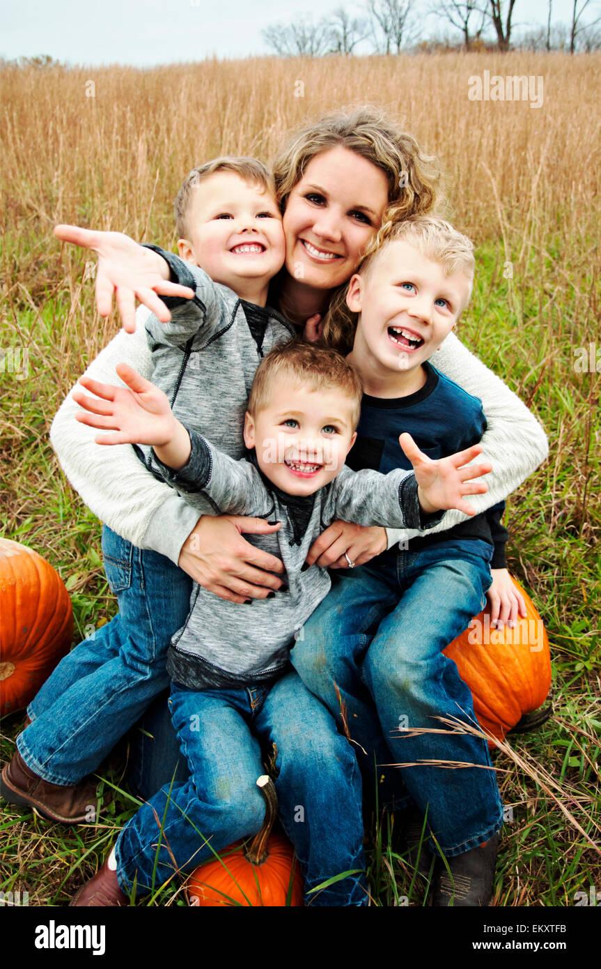 Madre sosteniendo a tres muchachos en sus brazos Imagen De Stock