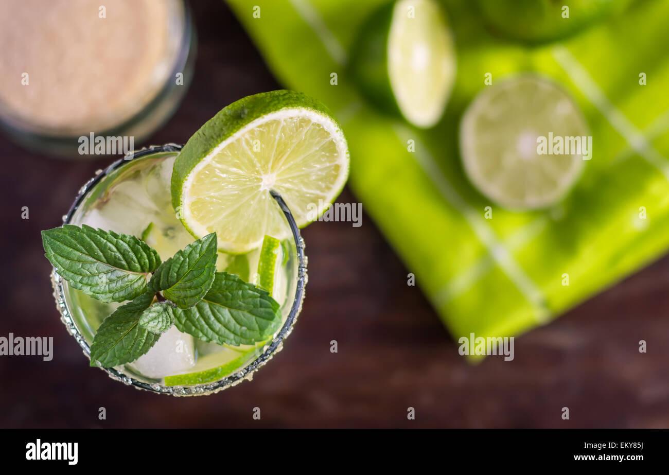 Lime Mojito bebida alcohólica cóctel en mesa de madera de sobrecarga Imagen De Stock