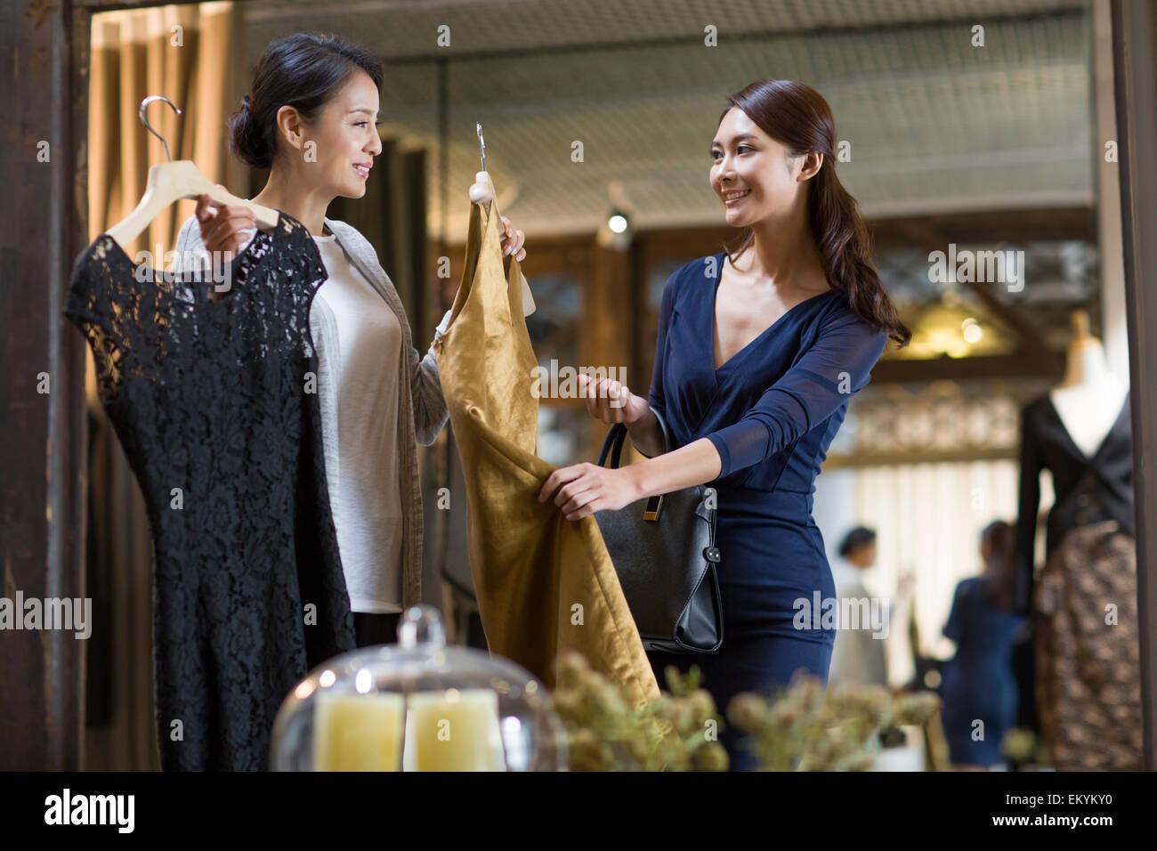 El propietario de una tienda de ropa ayudando al cliente a elegir vestido Imagen De Stock