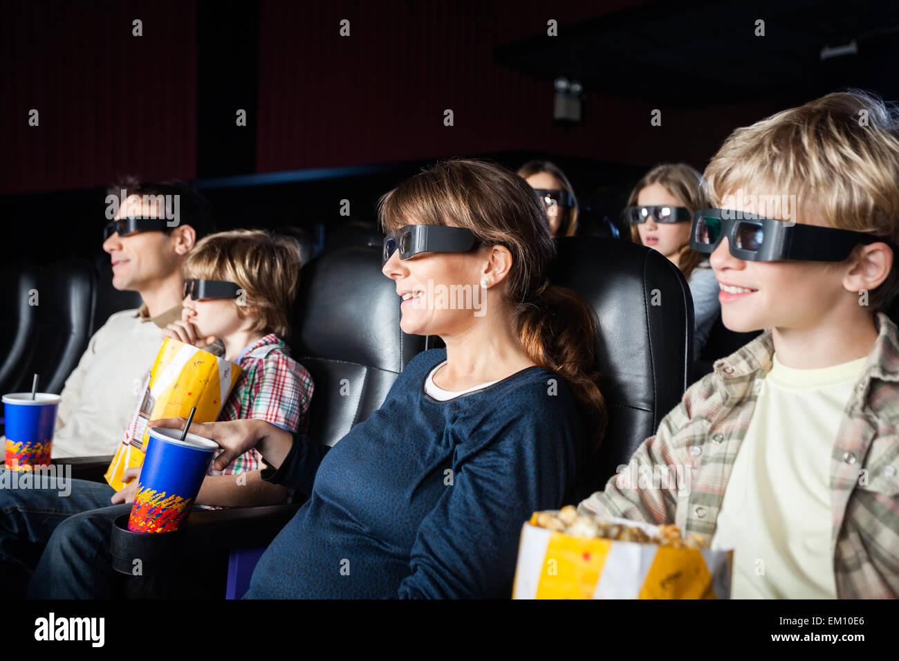 Las familias sonrientes viendo películas en 3D en el teatro Imagen De Stock