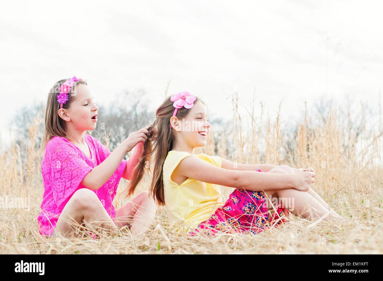 Chica trenzar el cabello de la hermana en la pradera Imagen De Stock