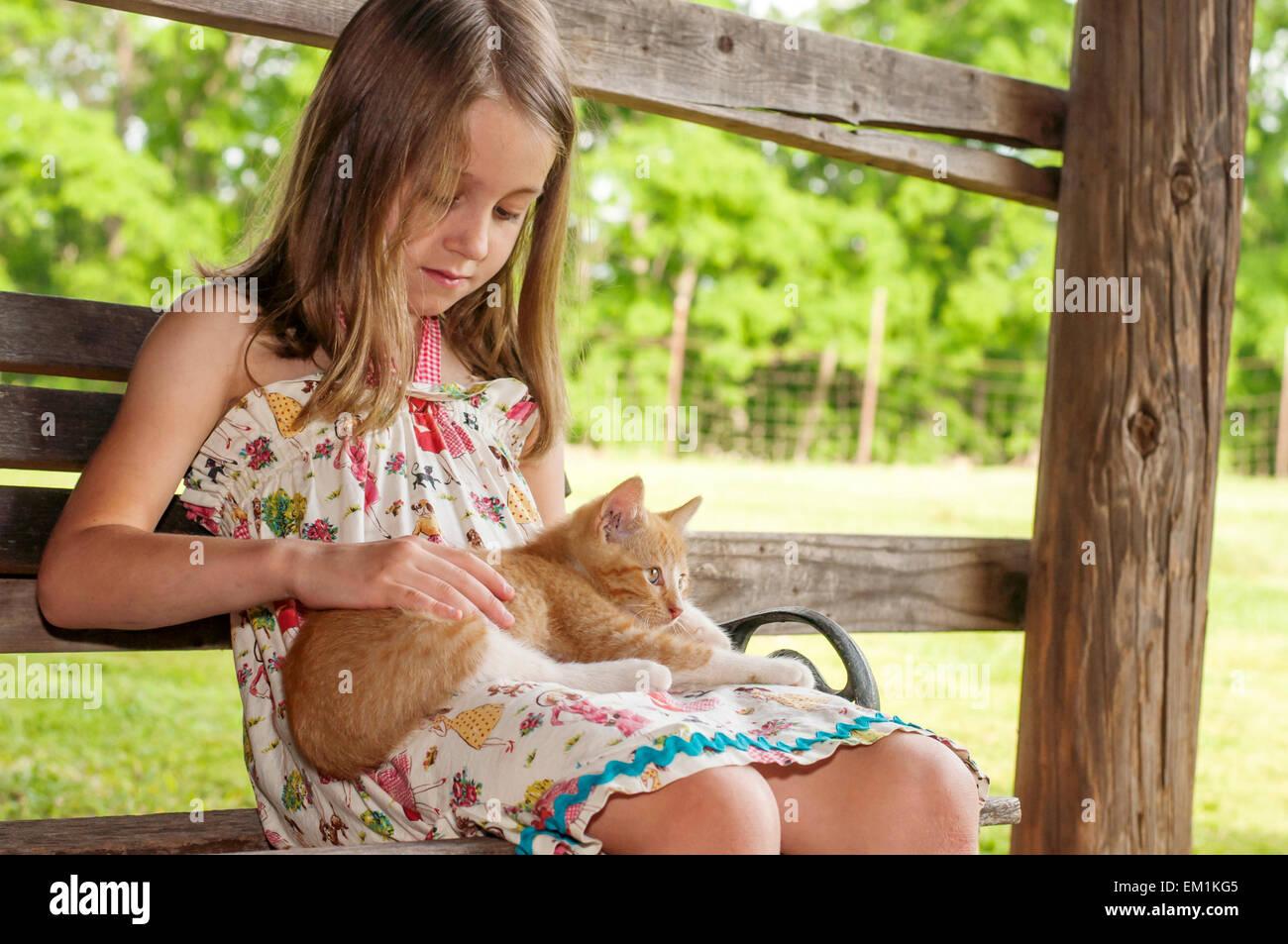 Chica acariciándole gatito en establo Imagen De Stock