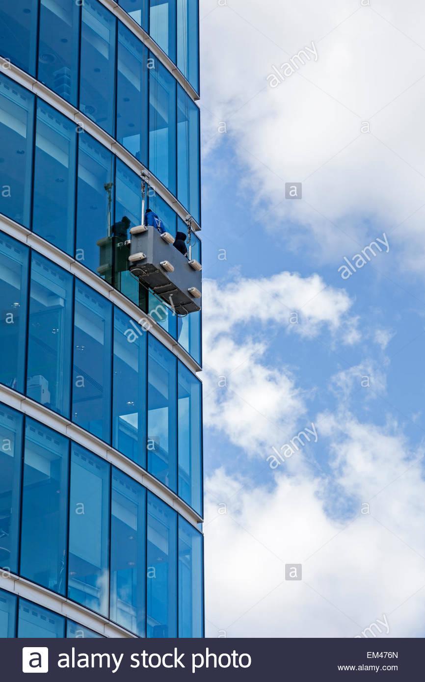 Limpieza de cristales de un alto edificio de oficinas con el uso de una cuna. Imagen De Stock
