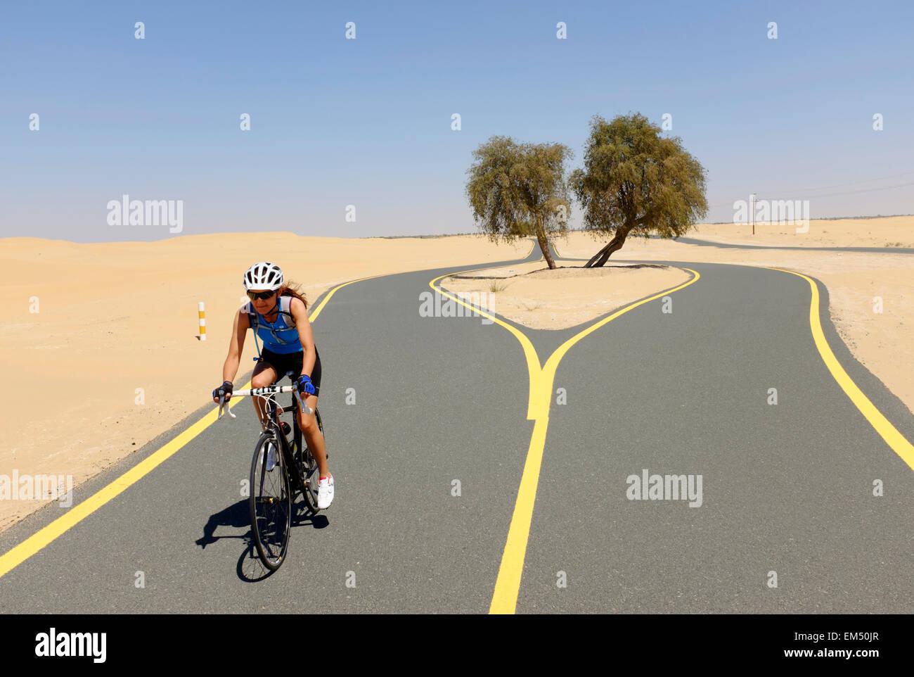 Ciclista femenina de nuevo desierto ciclo pista en Al Qudra en Dubai, Emiratos Árabes Unidos Foto de stock
