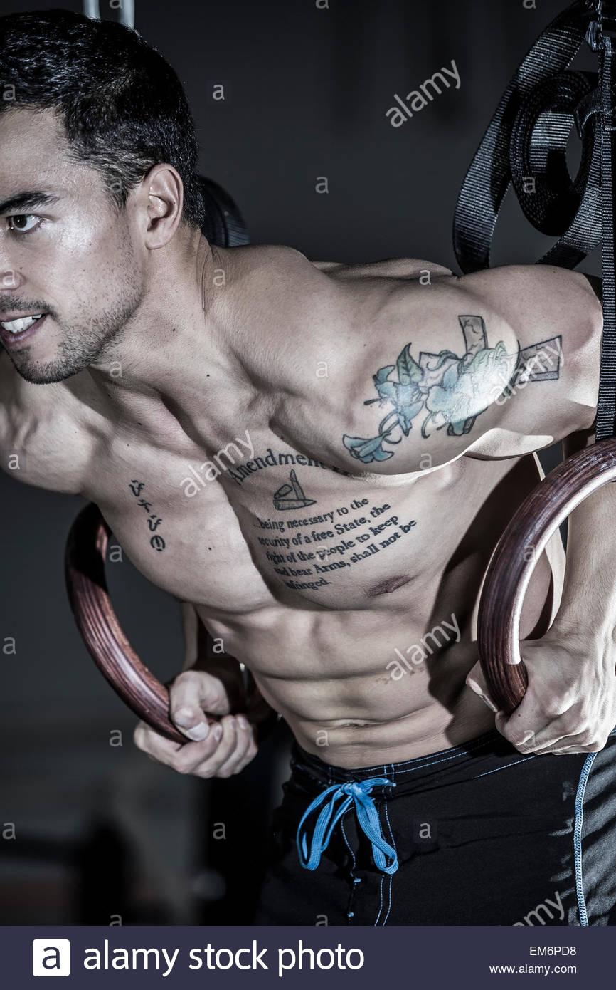 Un levantador de pesas y CrossFit descamisado macho deportista realiza un músculo en un gimnasio CrossFit. Imagen De Stock