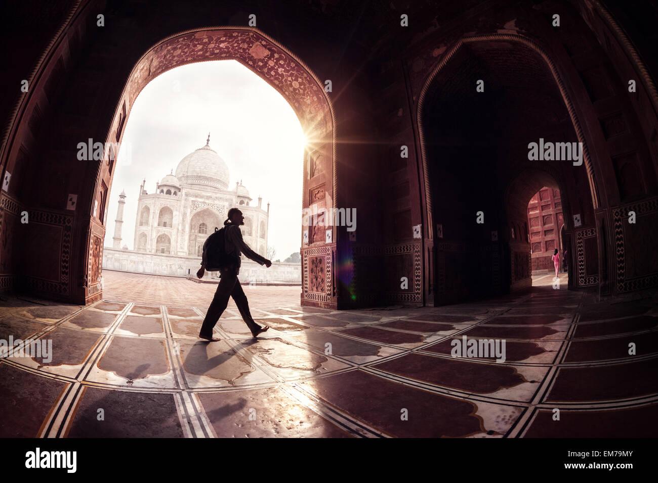 Turista con mochila caminando en la mezquita arch cerca del Taj Mahal en Agra, Uttar Pradesh, India Imagen De Stock
